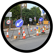 Traffic management signs setup in a picture cropped into a circle with a black outline