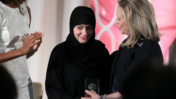 WASHINGTON, DC - MARCH 08:  Political activist Samar Badawi (C) of Saudi Arabia is presented with an International Women of Courage Award by U.S. Secretary of State Hillary Clinton (R) as first lady Michelle Obama looks on during a ceremony at the State Department March 8, 2012 in Washington, DC. Ten women from around the world were presented with the awards during the sixth annual ceremony to recognize their courage and leadership.  (Photo by Alex Wong/Getty Images)
