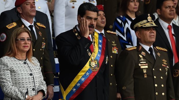Venezuelan President Nicolas Maduro (C) gestures next to his wife Cilia Flores (L) during a ceremony to celebrate the 81st anniversary of the National Guard in Caracas on August 4, 2018 day in which Venezuela's controversial Constituent Assembly marks its first anniversary. - The Constituent Assembly marks its first anniversary on August 4 as the embodiment of Maduro's entrenchment in power despite an economic crisis that has crippled the country's public services and destroyed its currency. The assembly's very creation last year was largely responsible for four months of street protests that left some 125 people dead. (Photo by Juan BARRETO / AFP)        (Photo credit should read JUAN BARRETO/AFP/Getty Images)