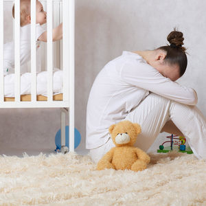 Postpartum Depression mom near baby crib