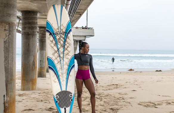 woman posing with surfboard on beach getting ready for workout