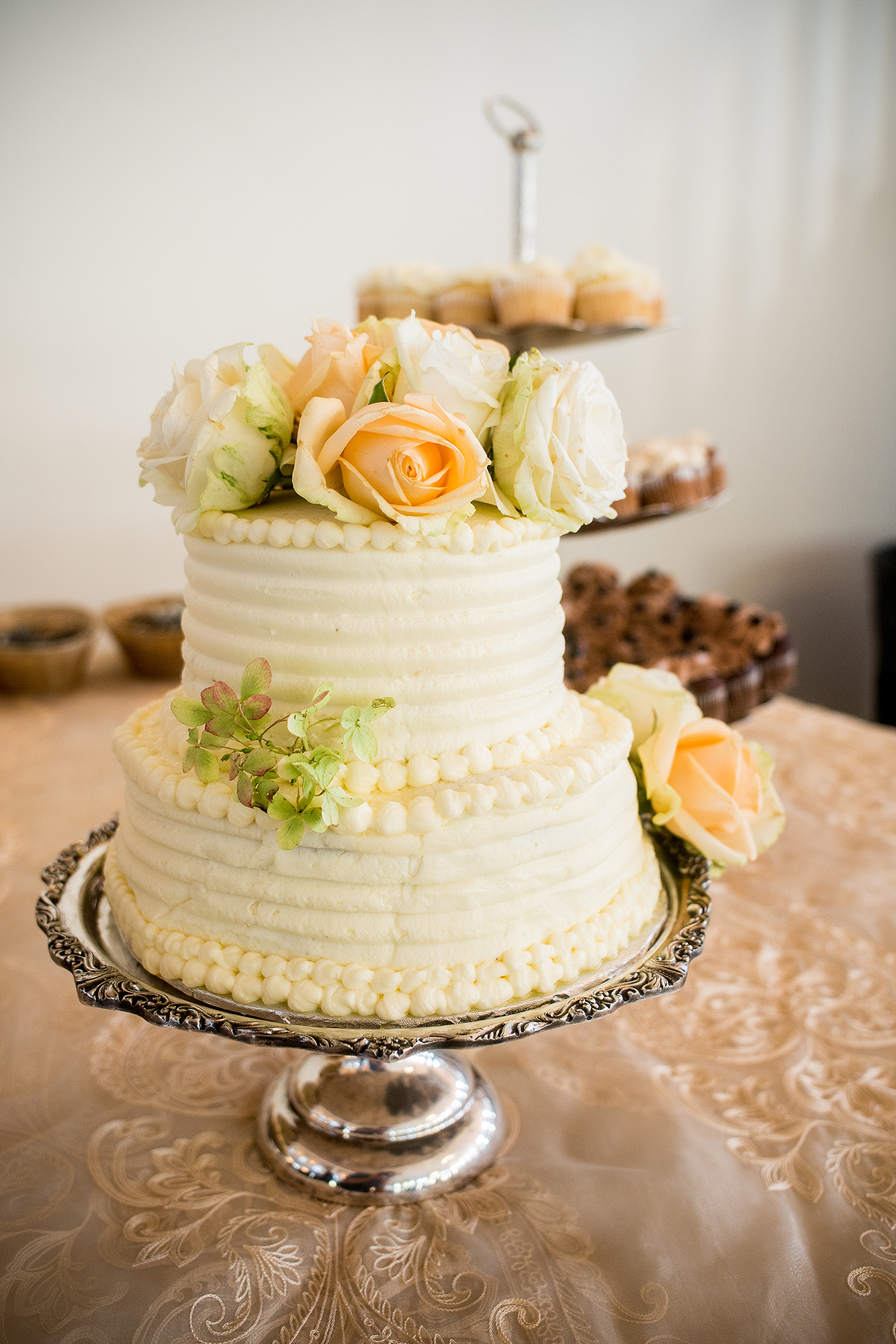 small wedding cake with yellow gold flowers and cream colored icing