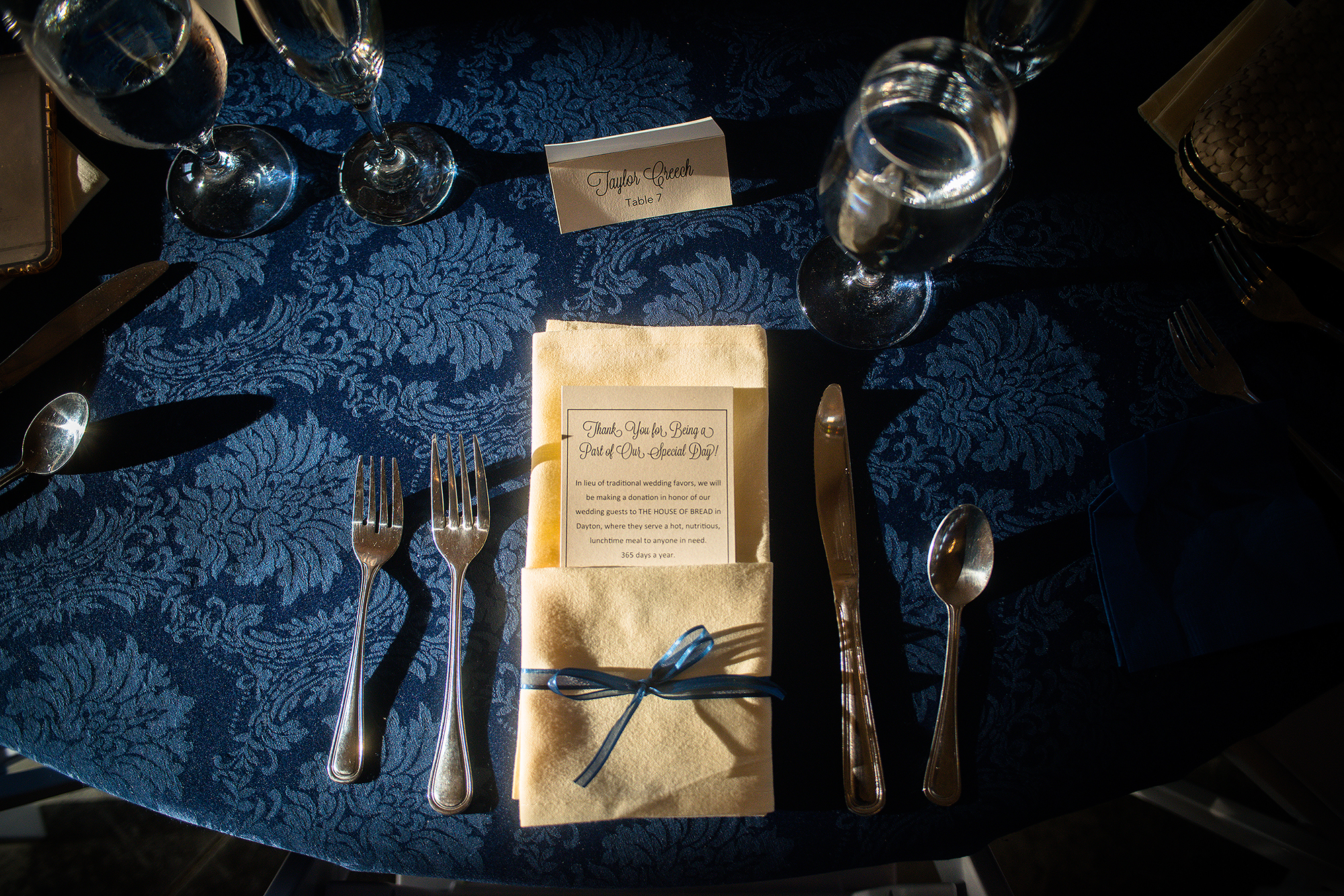 table setting at Rosewood with blue patterned table cloth and beige napkins