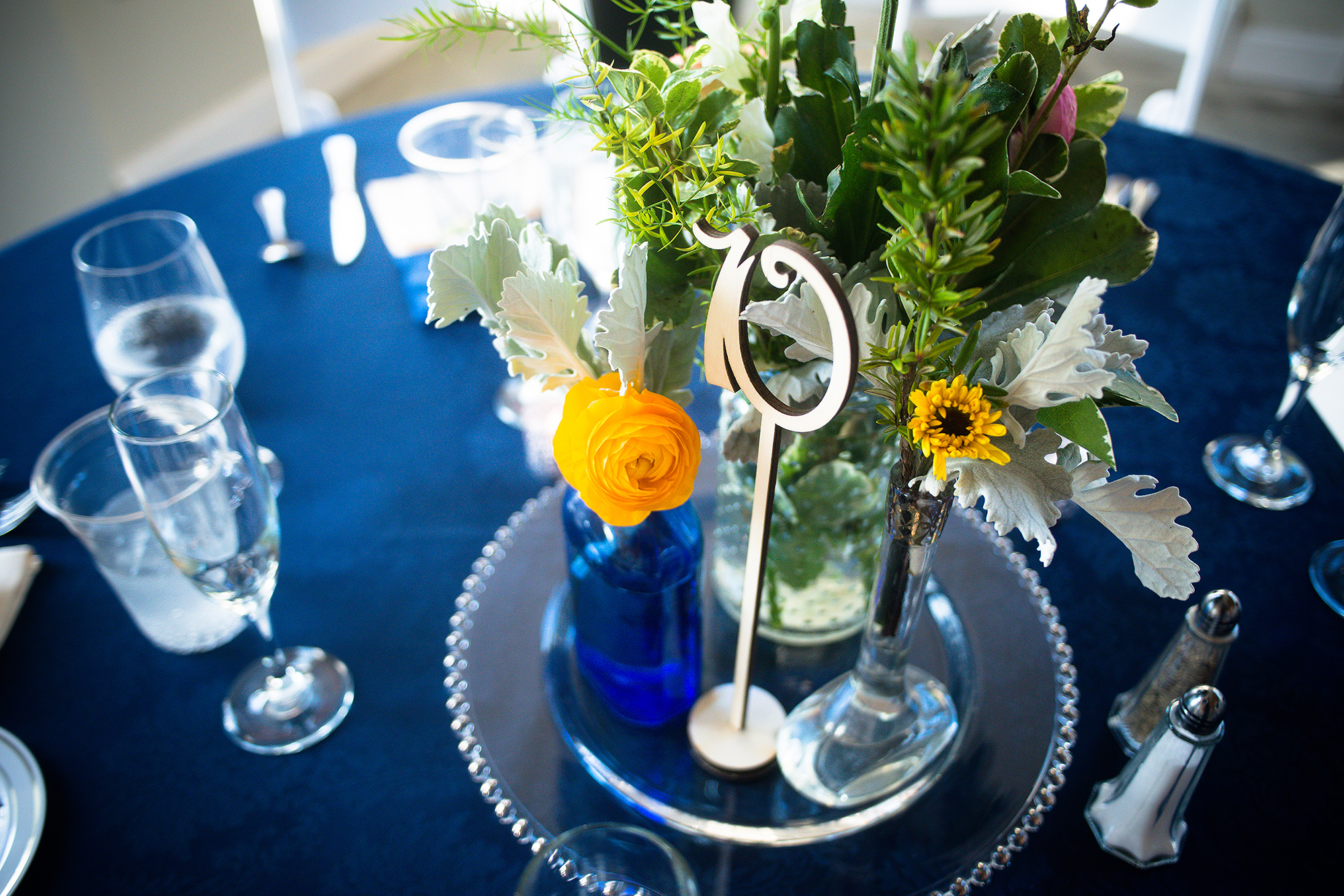 table center piece with place numbers and flowers of green and gold