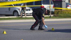 Kanadischer Polizeibeamter sichert Spuren auf einer Straße nach einer Schießerei.