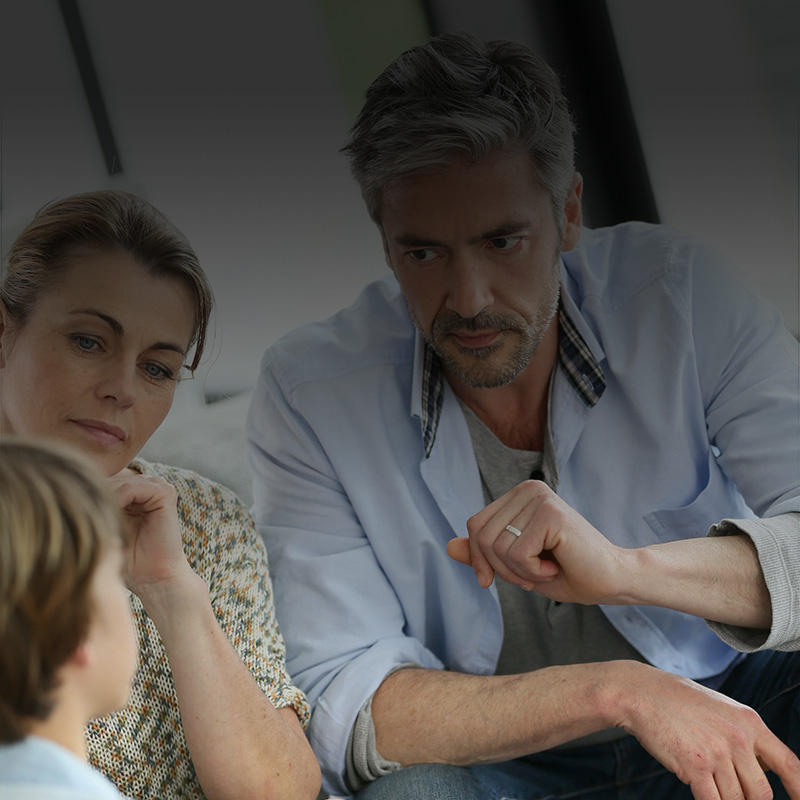 Picture of a family, mother father and son, having a serious conversation.