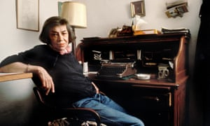 Patricia Highsmith in jeans, with short hair, leaning against a shelf while sitting at her old wooden desk with a typewriter