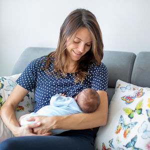 Polka Dot Shirt Mother Breastfeeding Child on Sofa