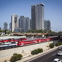 Illustrative: An Israel Railways train passes the Ayalon Highway, near the Arlozorov Street 'Central' train station in Tel Aviv, August 23, 2016. (Miriam Alster/Flash90)