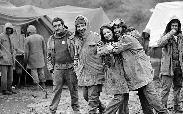 Israeli soldiers at the Syrian ceasefire line in the Golan Heights are seen, October 31, 1973, after sudden cold, rain and fog hit them.  Female soldier is radio operator Zehava Mizrachi.  Other soldiers are unidentified. (AP Photo)