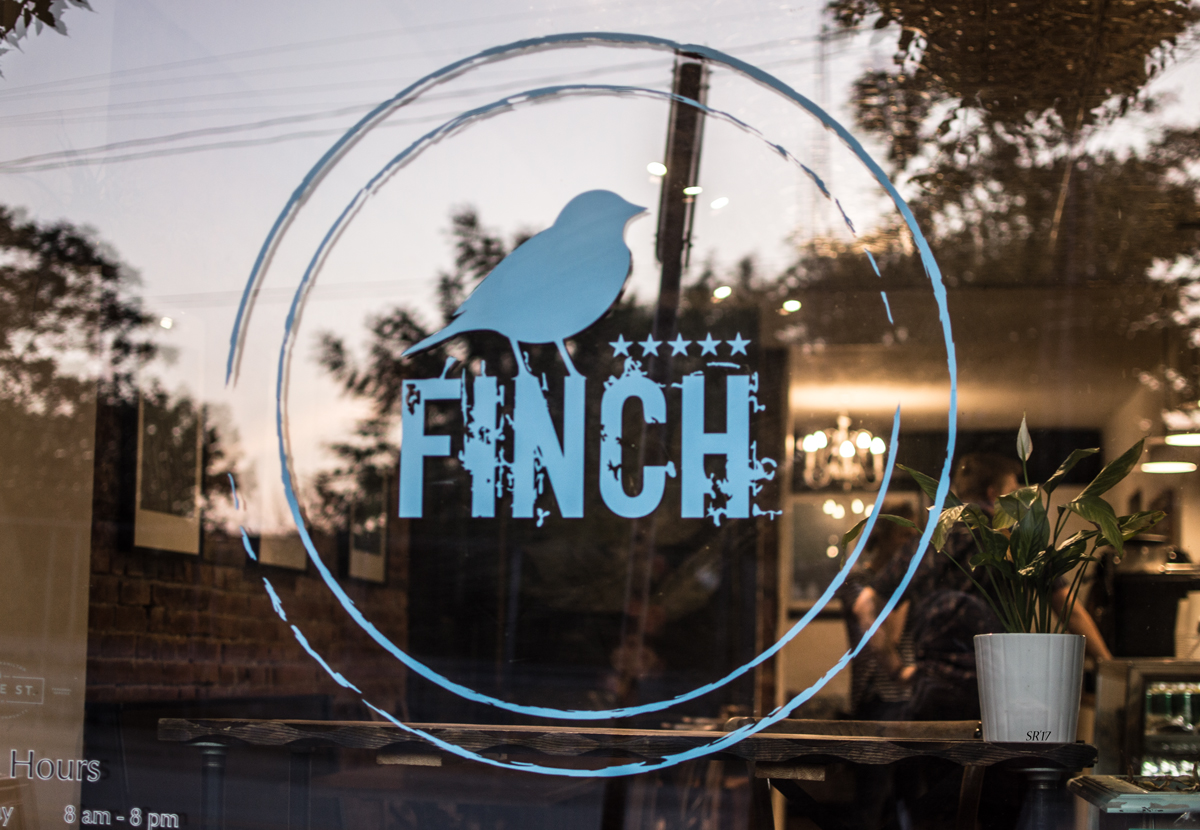 """Storefront that says """"FINCH"""" with a blue bird"""