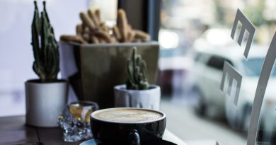 latte in coffee mug on counter by window