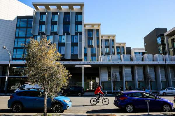 A bicylist passes by an apartment building on Channel Street in the Mission Bay neighborhood of San Francisco, California, on Thursday, Jan. 26, 2017.