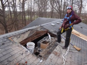 image of maria standing on roof next to hole in roof where the old chimney used to be