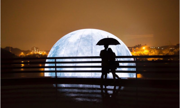The silhouette of a couple against a giant, illuminated model of the Moon. Photo: China News Services