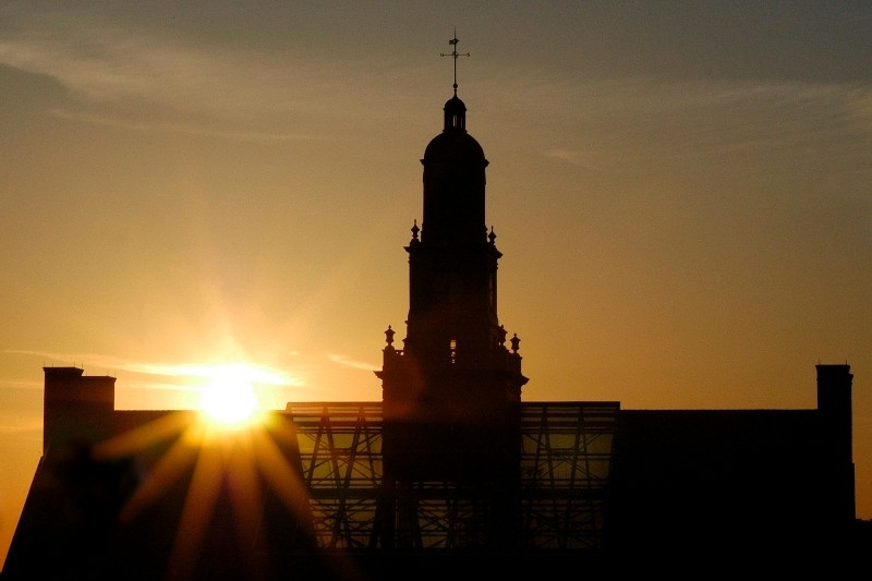 The sun setting behind UC's McMicken Hall
