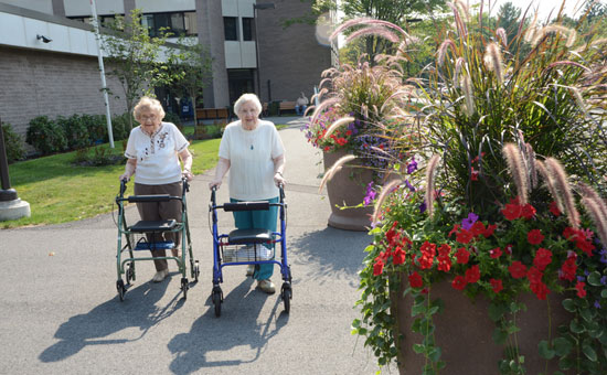 Two elderly residences walking outside with walkers