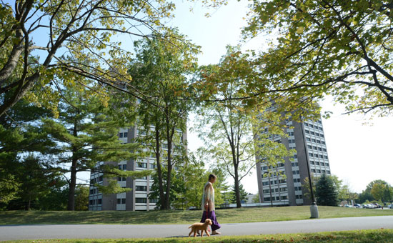Women walking with her dog in front of apartment buildings