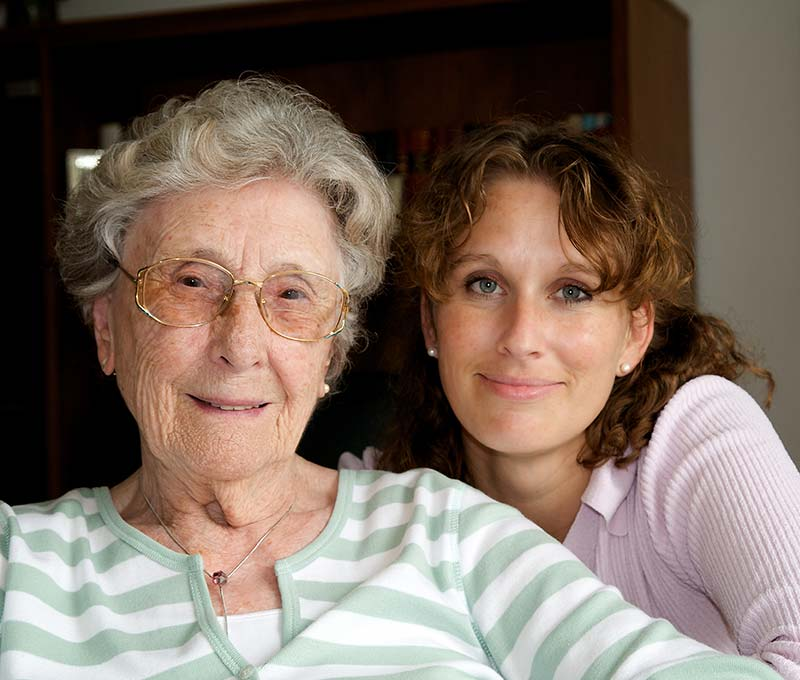 an elderly woman with glasses sitting inside with her daughter