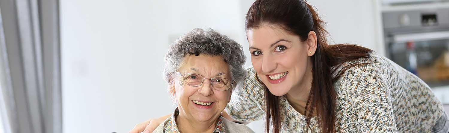 a female caregiver with her arm around a senior woman