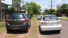 Cars parked on a residential verge outside a house.