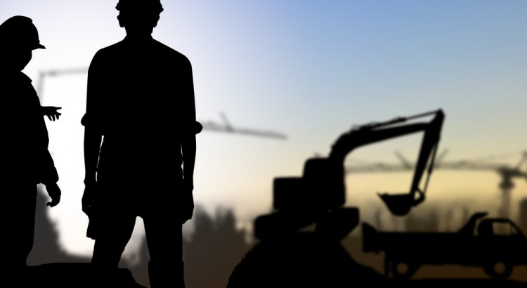 silhouette engineer looking Loaders and trucks in a building site over Blurred construction worker on construction site