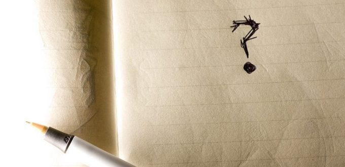 This is a picture of a pen siting on a notebook with a question mark on one of the pages.