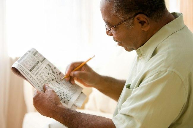mature man working crossword