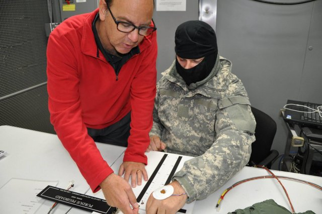 Inside the U.S. Army Research Institute of Environmental Medicine, or USARIEM, environmental chamber, a room that can simulate cold weather conditions, Dr. John Castellani, the principal investigator, instructs a study volunteer on how to take the Purdue Pegboard Test, a test that measures hand dexterity. The study is part of an effort to develop technology that can warm the hands and fingers without obstructing them.