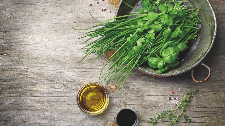 frische Kräuter mit Basilikum und Schnittlauch und Petersilie auf einem Teller neben Öl und Essig auf einem Holztisch