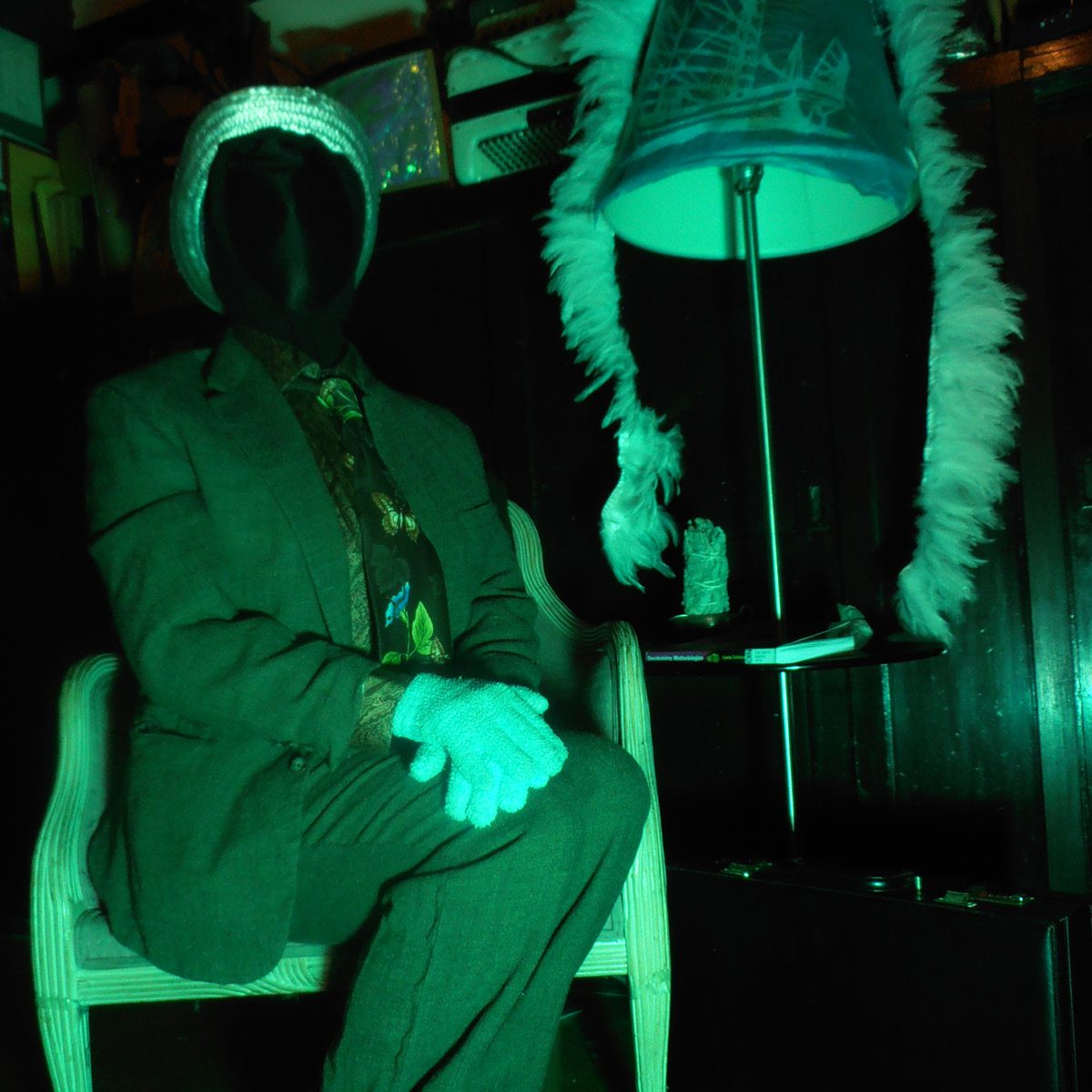 Image of person sitting in a chair with hands cross on their knees next to a table lamp. There is a teal lighting overall.
