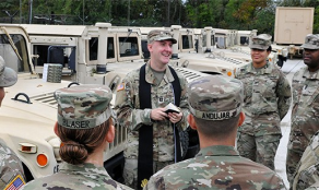 Chaplain Fuller gives a field service next to some HUMVEES.