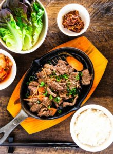 Bulgogi served with rice, lettuce, kimchi and dipping sauce