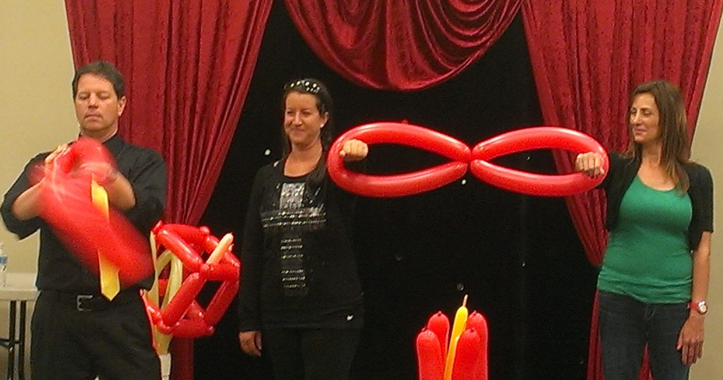 Balloon artist Dale Obrochta entertaining family at library program.  Art of Inflation, balloon show for libraries.