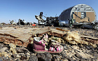 A child's shoe is seen in front of debris from a Russian airliner which crashed at the Hassana area in Arish city, north Egypt