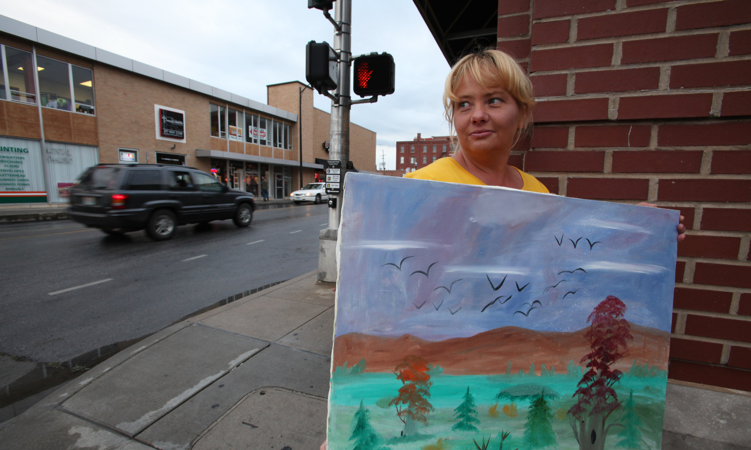 Jammie Russell holds up one of her paintings, a simple nature scene. Some of her art reflects real locations. This one is entirely of Russell's imagination.