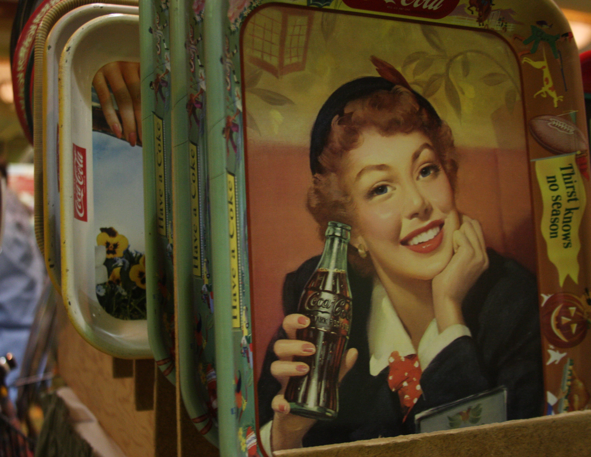 Serving trays, in their heyday, were both works of art and ways to carry Coca-Cola from the kitchen to the table or the back yard. The company created hundreds of different trays — almost always featuring a red-haired female model.