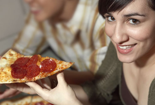 Woman eating greasy pepperoni pizza