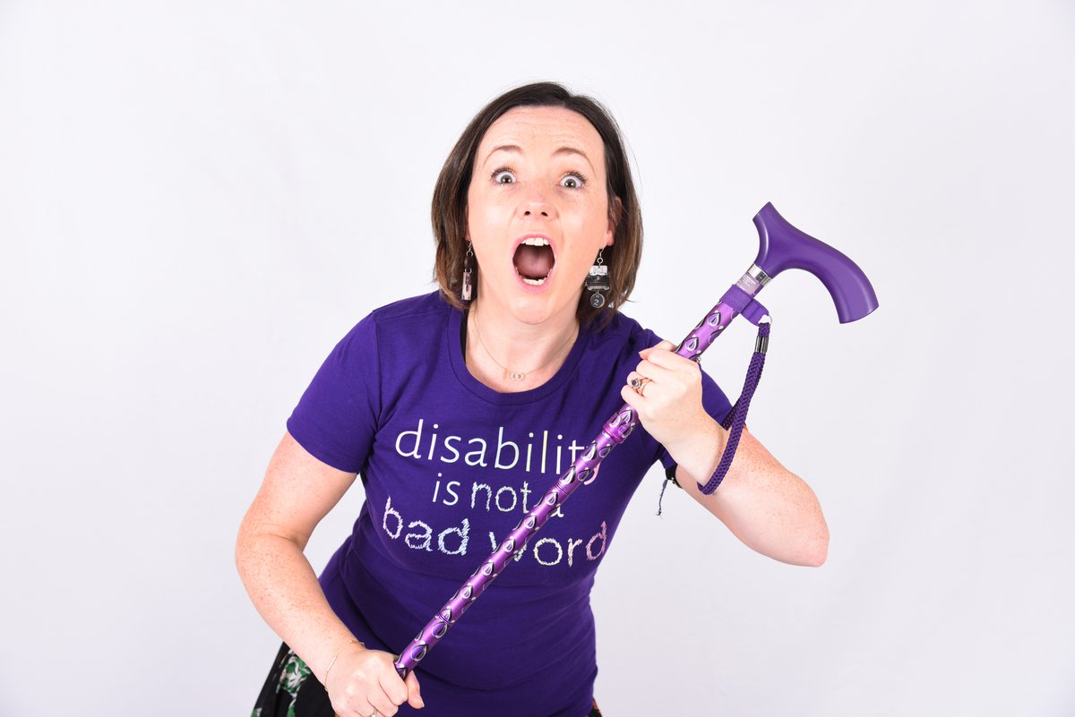Lisette in a purple t-shirt which reads 'disability is not a bad word', holding her purple walking stick with her eyes and mouth wide open. photo credit: Laura Tindall at PaperBoat Photography