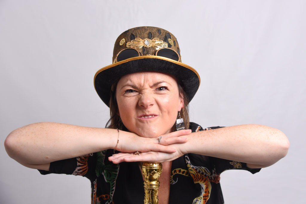 Woman wearing gold hat resting head and arms on a cane