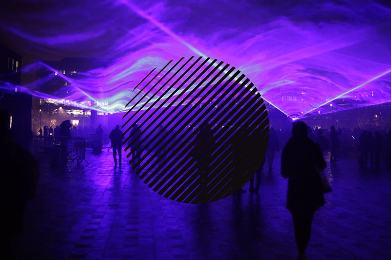 A mysterious image of smoke and purple laser lights with people walking in silhouette and a black circular graphic laid over the photo