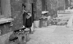 1950s. Small boy with mother in the doorway of run-down Victorian terraced house, in this historical picture by J Allan Cash.