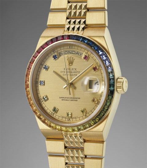 A highly rare, attractive and unusual yellow gold and rainbow-colored multi-gem set tonneau-shaped calendar wristwatch with quartz movement and bracelet
