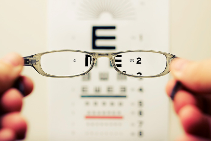 A person holding up a pair of glasses to an opticians eye chart - autofocus issues
