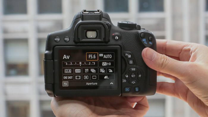 A photographer using exposure compensation on a DSLR camera