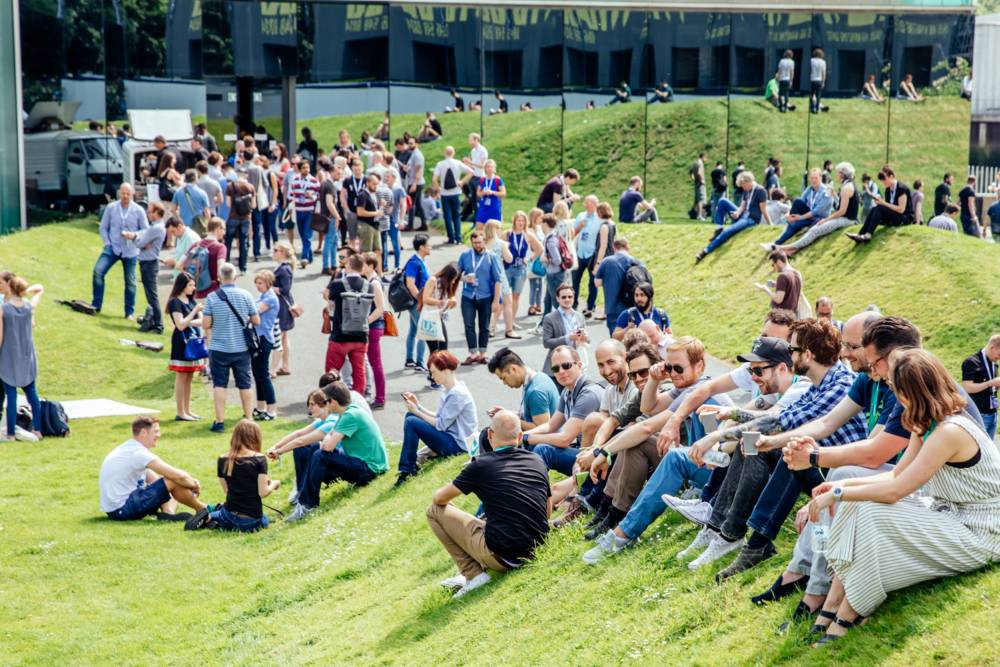 UX London attendees relax on the lawns outside and enjoy the sunshine.