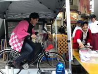 自転車型人力発電機のペダルをこぐ参加者