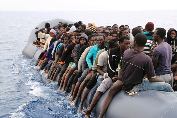 Migrants wait to be rescued from a sinking