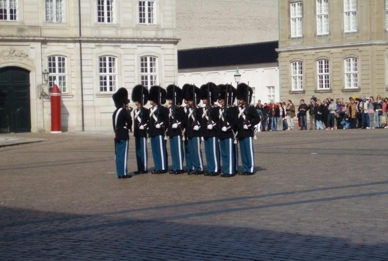 Changing of the guard in the large octagonal courtyard of the Amalienborg Palace in Copenhagen. The plaza is bordered by four buildings with identical facades, which serve as the winter home of the royal family.