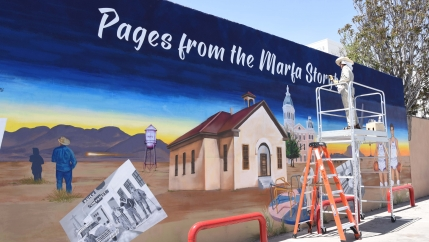 A painter works on a mural of a school building
